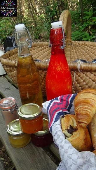 Petit déjeuner champêtre avec jus de pomme, confitures, miel et panier de croissants, pains au chocolat et petits pains